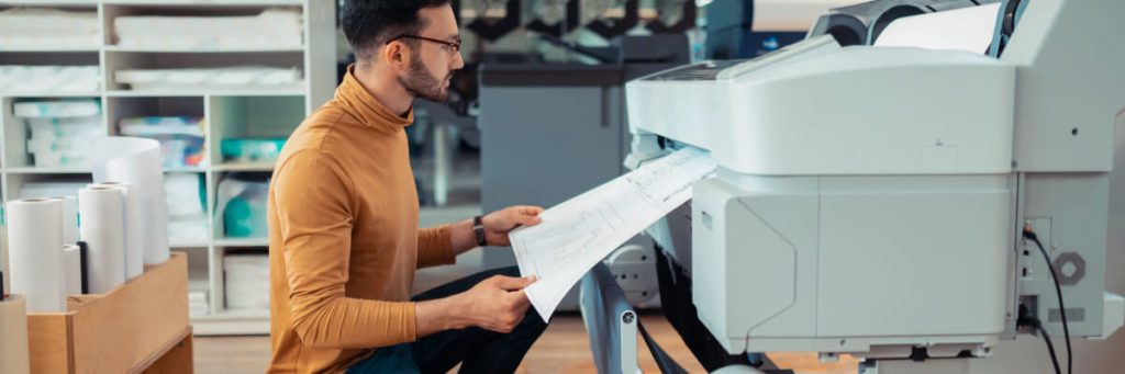 Man waiting while printing paper with sketches